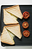Toasted cheese sandwiches and tomatoes on grill plate