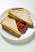 Toasted cheese sandwiches and grilled tomato on plate