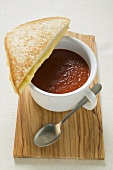 A cup of tomato soup with toasted cheese sandwich on board