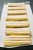 Several toasted cheese sandwiches in a row on paper