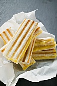 Several toasted cheese sandwiches on paper