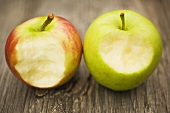 Two apples with bites taken on wooden background