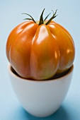 Tomato in bowl on pale blue background