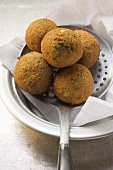 Falafel (chick-pea balls) on slotted spoon
