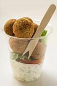 Falafel (chick-pea balls) with yoghurt sauce in beaker