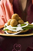 Woman serving falafel (chick-pea balls) with vegetables