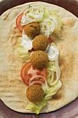 Falafel (chick-pea balls) with vegetables on flatbread