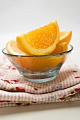 Several orange wedges in glass bowl on cloth
