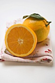 Whole orange with leaf and orange half on cloth