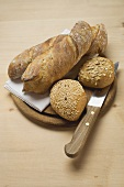 Baguettes and wholemeal rolls on breadboard with knife