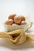Brown eggs in white bowl on paper