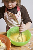 Small boy stirring cake mixture with whisk