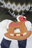 Child holding gingerbread rocking horse