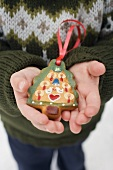 Child holding gingerbread Christmas tree (tree ornament)