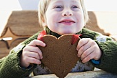 A small boy with a Christmassy gingerbread heart