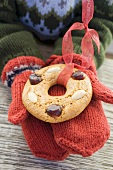Child's hands in mittens holding gingerbread tree ornament
