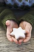 Kinderhände halten Zimtstern