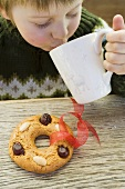 Small boy drinking hot drink, gingerbread tree ornament