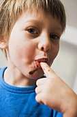 Small boy licking chocolate from his finger