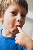 Kleiner Junge nascht Schokoladensauce
