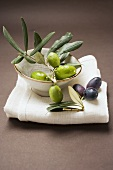 Olive sprig with green olives in bowl, black olives on cloth