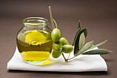 Green olives on twig beside jar of olive oil