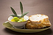 Olive sprig with green olives in bowl of olive oil, white bread