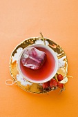 Rose hip tea with tea bag in china cup