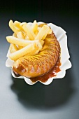 Currywurst (sausage with ketchup & curry powder) & chips on paper dish