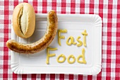 Sausage with bread roll and 'Fast Food' written in mustard