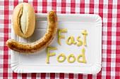 Bratwurst mit Brötchen und Senf (Schriftzug Fast Food)