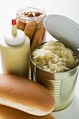 Bread roll, sauerkraut in tin, mustard, frankfurters in jar