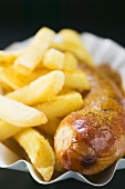 Currywurst (sausage with ketchup & curry powder) & chips in paper dish