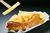 Sausage with ketchup & curry powder & chips, one on wooden fork