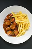 Currywurst (sausage with ketchup & curry powder) & chips on plate