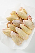 Fresh chicken wings on paper