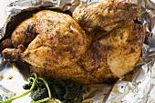 Half a roast chicken in aluminium foil