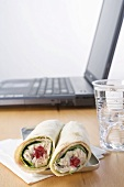 Tuna wraps and mineral water in front of laptop