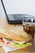 Sub sandwich and cola in front of laptop