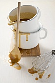 Gravy in an enamel jug, wooden spoon, whisk