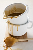 Gravy in an enamel jug, wooden spoon beside it