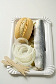 Herring with gherkins, onions & bread roll on paper plate