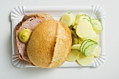 Leberkäse in roll with mustard & potato salad on paper plate