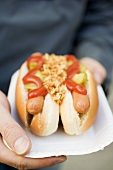 Hands holding hot dogs on paper plate