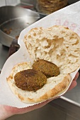 Hand holding pita bread filled with falafel (chick-pea balls)