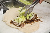 Making a döner wrap (topping with lettuce)