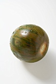 Green striped tomato with drops of water