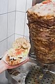 Hand holding a döner kebab (opened), meat on spit