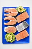 Fresh salmon cutlets and salmon fillets on chopping board