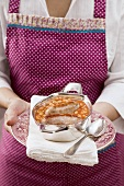 Woman serving baked beans & sausages in serving dish on plate